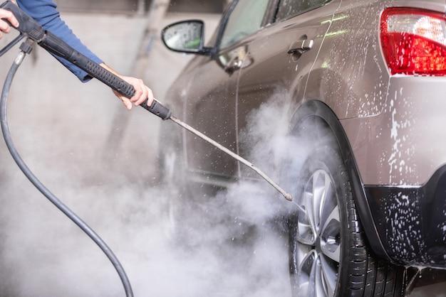 Manuelle autowäsche mit druckwasser in der autowäsche draußen. Premium Fotos