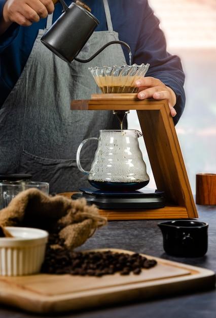 Manueller handbrühkaffee. barista gießt wasser über gemahlenen kaffee, papierfilter und sammelt ihn in einem glasbehälter unter einem holzhalter. Premium Fotos
