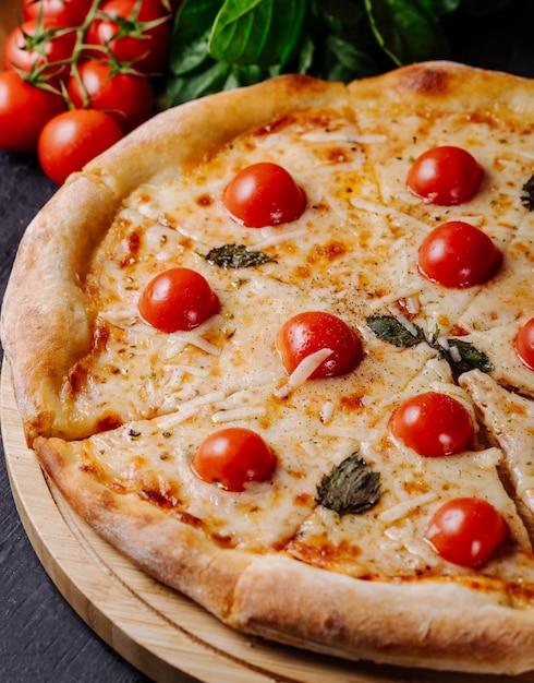 Margarita-pizza mit kirschtomaten und basilikumblättern. Kostenlose Fotos