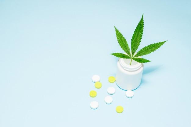 Marihuanablatt in der medizinischen pillenflasche auf blau. Premium Fotos