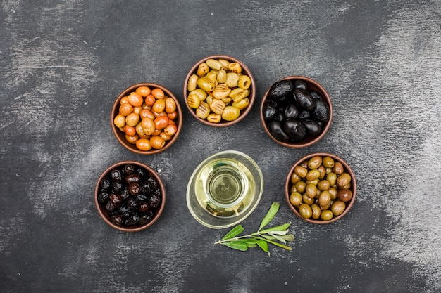 Marinierte oliven und olivenöl in tonschalen und glas mit olivenbaumzweig draufsicht auf dunkelgrauem schmutz Kostenlose Fotos