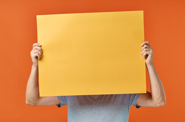 Marketingplakat orange wandmann in der wand beschnittene ansicht Premium Fotos