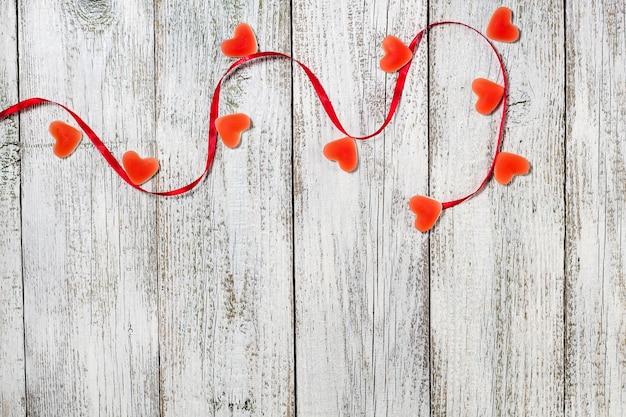 Marmelade süßigkeiten form herz und rotes band auf holztisch, valentinstag zusammensetzung, grußkarte. Premium Fotos