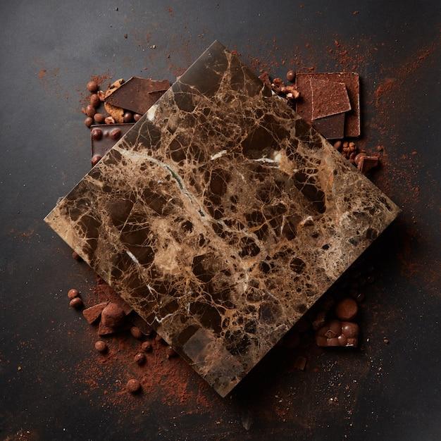 Marmortafel für text und schokoladenpulver an einer schwarzen wand Premium Fotos