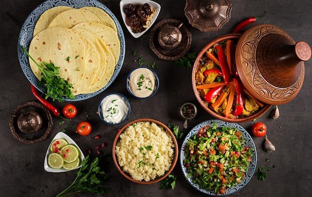 Marokkanisches essen. traditionelle tajine-gerichte, couscous und frischer salat auf rustikalem holztisch. tajine hühnerfleisch und gemüse. arabische küche. ansicht von oben. flach liegen Premium Fotos