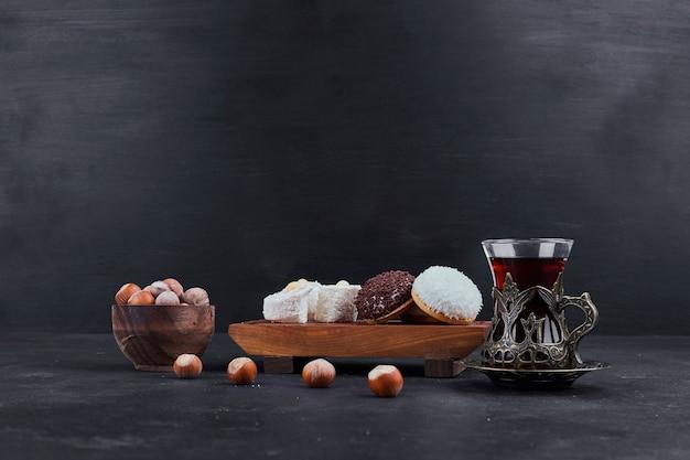 Marshmallow-kekse auf einer holzplatte und ein glas tee mit nüssen herum. Kostenlose Fotos
