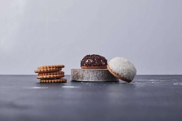 Marshmallow-kekse mit schokolade und kokosnusspulver auf einem stück holz auf blau. Kostenlose Fotos