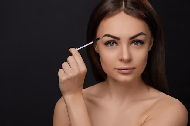 Mascara, beauty make-up, frische, weiche haut und lange, schwarze, dicke wimpern, die mascara mit einem kosmetikpinsel auftragen, wimpernverlängerung, künstliche wimpern, Premium Fotos