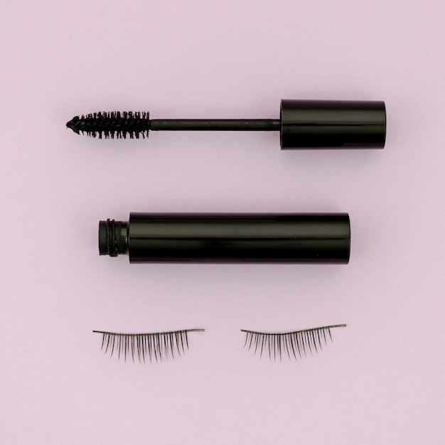 Mascara und falsche wimpern auf lila hintergrund Kostenlose Fotos