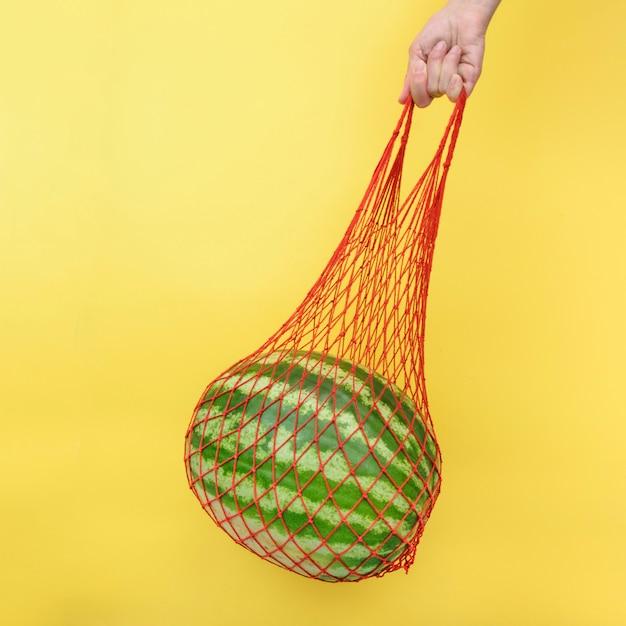 Maschenshoptasche mit wassermelone auf gelbem hintergrund. null abfall, umweltfreundliches plastikfreies konzept. gesundes diät- und detoxkonzept der sauberen ernährung Premium Fotos