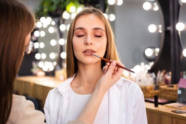 Maskenbildner, der lippenstift auf lippen unter verwendung des pinsels aufträgt Kostenlose Fotos