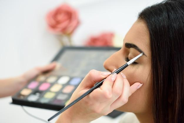 Maskenbildner, der make-up auf die augenbrauen einer frau setzt Premium Fotos