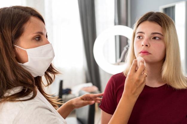 Maskenbildner tragen maske und setzen lippenstift auf kunden Kostenlose Fotos
