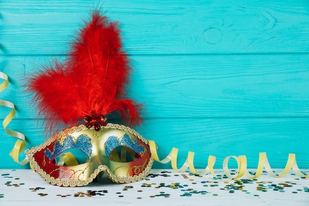 Maskeradekarnevalsfedermaske mit gelbem ausläufer und konfetti Kostenlose Fotos