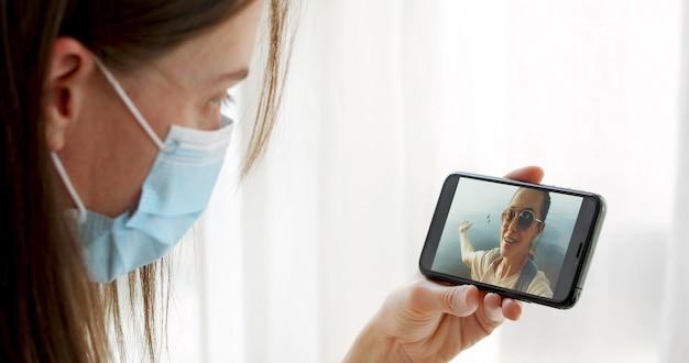 Maskierte frau, die auf videoanruf mit ihrer freundin spricht Premium Fotos