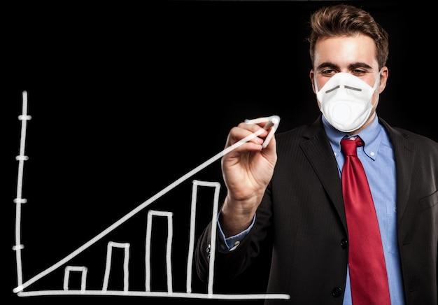 Maskierter mann, der eine positive diagramm-, coronavirus-geschäftskonzeptgelegenheit zeichnet Premium Fotos
