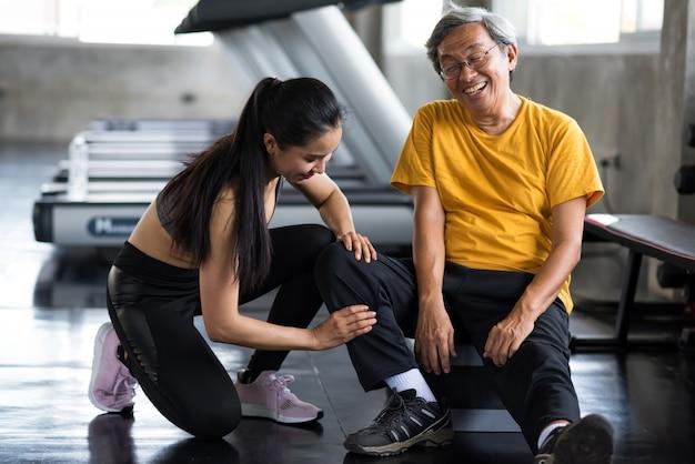 Massagebein des alten mannes durch mädchen in der turnhalle Premium Fotos