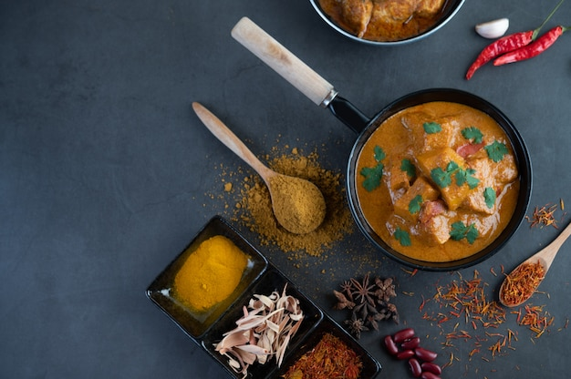 Massaman curry in einer pfanne mit gewürzen auf dem zementboden Kostenlose Fotos