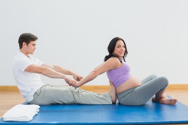 Masseur, der die arme und die schultern der schwangeren frau ausdehnt Premium Fotos