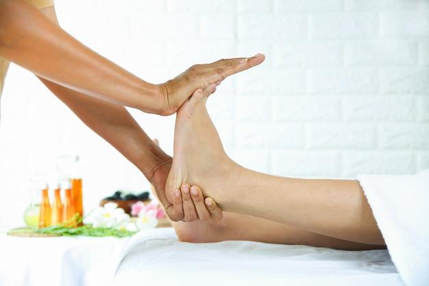Masseurin verwenden zwei hand-zu-fuß-massage mit junger frau Kostenlose Fotos
