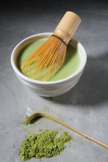 Matcha latte des grünen tees mit bambus-chasen und bambuslöffel in einer schüssel Premium Fotos