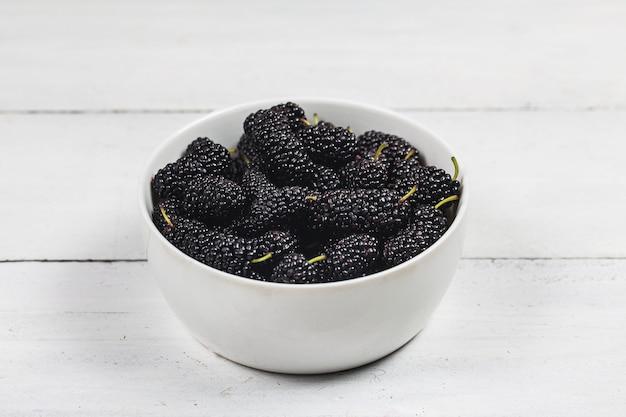 Maulbeerfrucht in der weißen schüssel auf hölzerner tabelle Premium Fotos