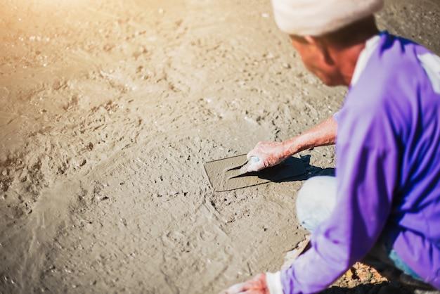 Maurer, der beton mit kelle planiert, die hände, die gegossenen beton ausbreiten. Premium Fotos
