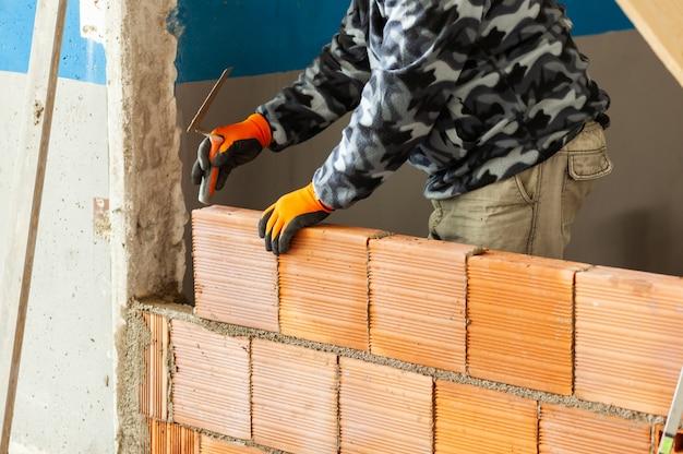 Maurer, der ziegelsteinmauerwerk auf innenwand installiert. Premium Fotos