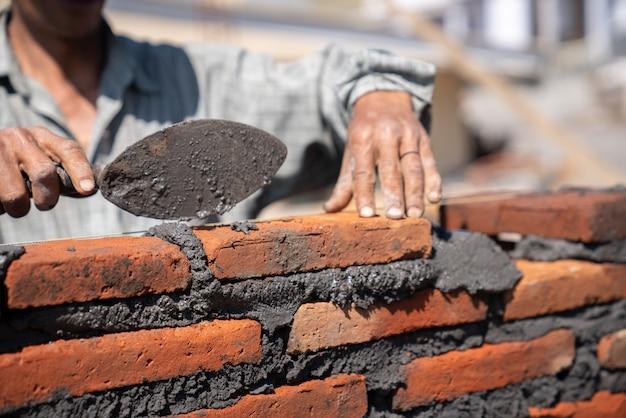 Maurerindustriearbeiter, der ziegelsteinmauerwerk mit kellenkittmesser an der baustelle installiert Premium Fotos