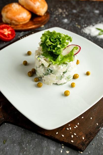 Mayonnaisesalat mit grünen erbsen auf einer weißen platte Kostenlose Fotos