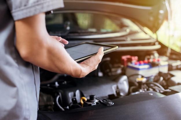 Mechaniker benutzt eine tablette, um den motor zu überprüfen Premium Fotos