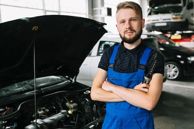 Mechaniker, der auto an der garage repariert Kostenlose Fotos