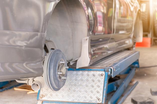 Mechaniker, der die achsmessvorrichtung an einem autoreifen eines neuen reifenaustauschs befestigt Premium Fotos