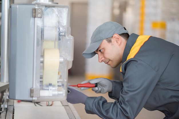 Mechaniker, der eine maschinerie in einer industriellen umgebung repariert Premium Fotos