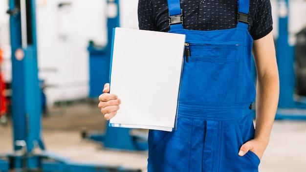 Mechaniker, der ordner mit sauberem papierblatt hält Kostenlose Fotos