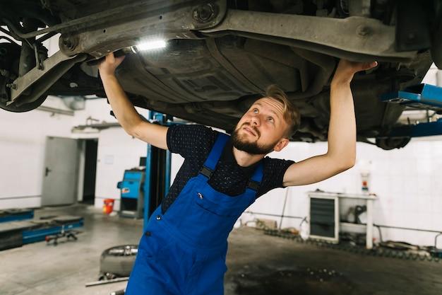 Mechaniker, die den wagenboden inspizieren Kostenlose Fotos