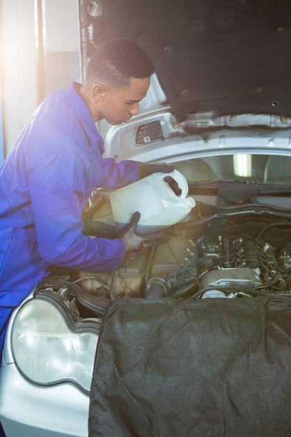 Mechaniker gießt öl schmiermittel in den automotor Kostenlose Fotos