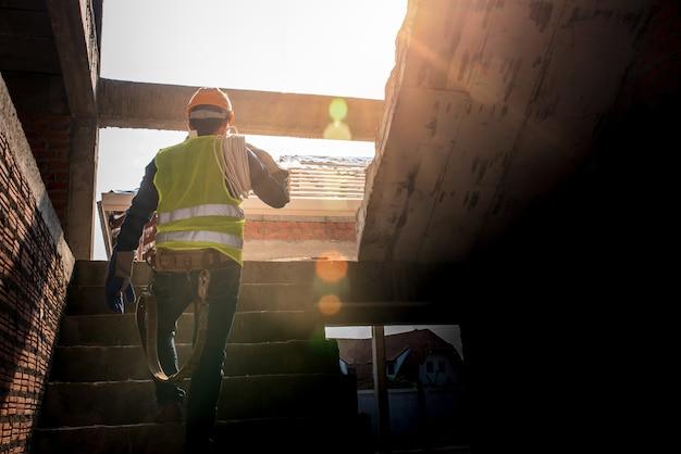 Mechaniker halten sie das weiße kabel mit persönlicher schutzausrüstung fest. beaufsichtigen sie den bau des hauses bauaufsichtsbeamte sehen innenausbau wohnbau Premium Fotos