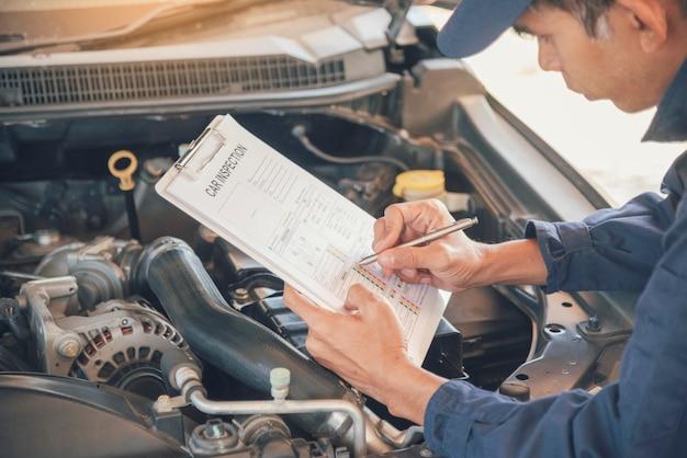 Mechanikermannhände, die auto im automobilautomobilzentrum fixieren. Premium Fotos