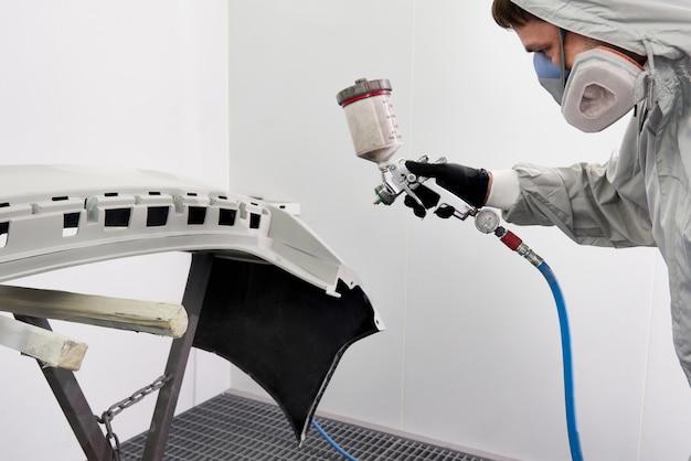 Mechanischer lackierstoßfänger eines autos mit sprühgerät in lackierkabine im reparaturautoservice Premium Fotos