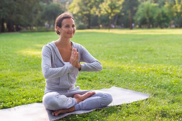 Meditierende haltung der seitenansichtsmiley-frau Kostenlose Fotos