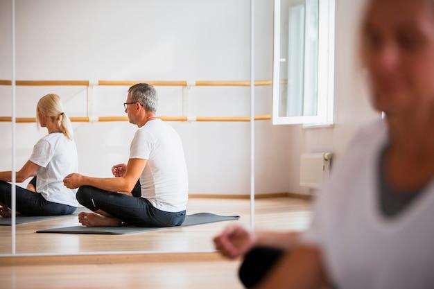 Meditierendes yoga des erwachsenen mannes und der frau Kostenlose Fotos