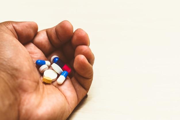 Medizin kapseln (verschiedene pillen) in der hand eines mannes. heller hintergrund. konzept der selbstmedikation, gesundheit, depression, krebs, medikamente. Premium Fotos