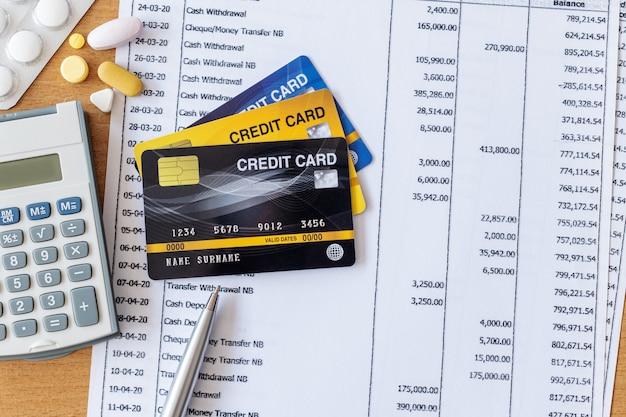 Medizin und taschenrechner auf kontoauszug und kreditkarte auf einem holztisch Premium Fotos