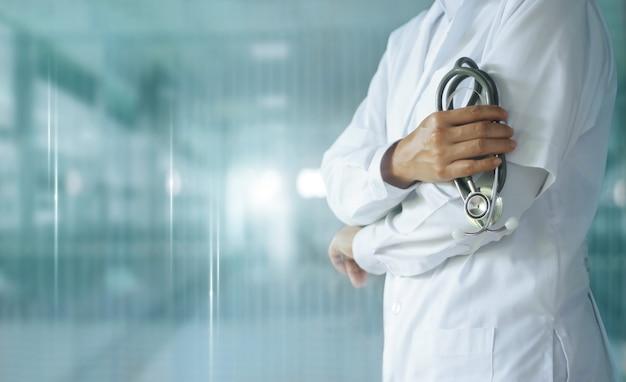 Medizinarzt mit stethoskop in der hand auf krankenhaus, medizintechnik. Premium Fotos