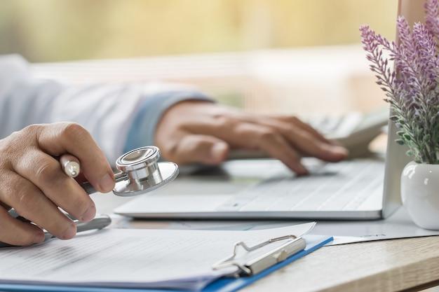 Medizindoktorhand, die stethoskope am beratungsraum, arbeitend an laptop-computer auf schreibtisch in der klinik hält Premium Fotos
