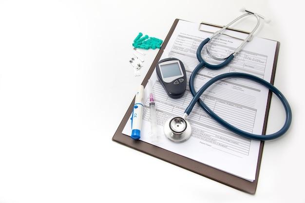 Medizinische ausrüstung auf weißem hintergrund. gesundheits- und medizinisches hintergrundkonzept. blutuntersuchungsgeräte für diabetes und blutzuckermessgerät Premium Fotos