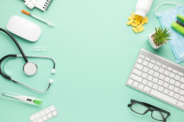 Medizinische ausrüstung und laptop mit saftiger anlage auf grünem pastellhintergrund Kostenlose Fotos
