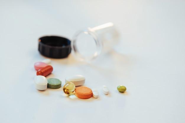 Medizinische bunte pillen, kapseln oder ergänzungen für die behandlung und das gesundheitswesen auf einem hellen hintergrund Premium Fotos