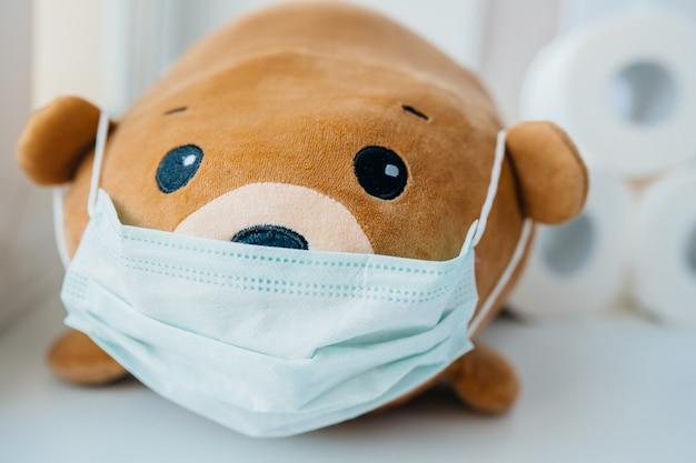 Medizinische einweg-gesichtsschutzmaske auf braunem teddybär Kostenlose Fotos